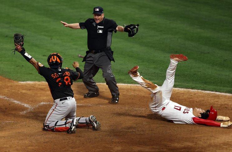 本塁生還で倒れ込みながら審判と一緒にセーフ©Getty Images