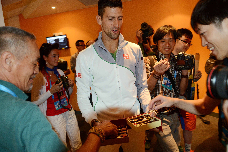 会見に集まった記者たちにチョコレートを配るジョコビッチ ©Getty Images